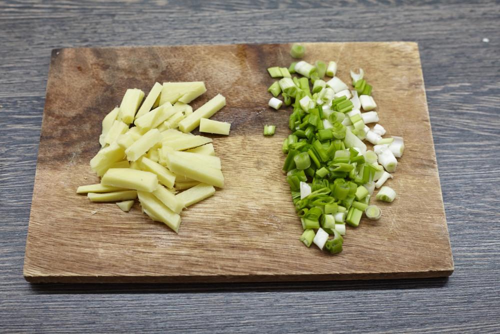 Рубим стебли лука и режем имбирь для легкого супа в азиатском стиле с гречневой лапшой и лососем.