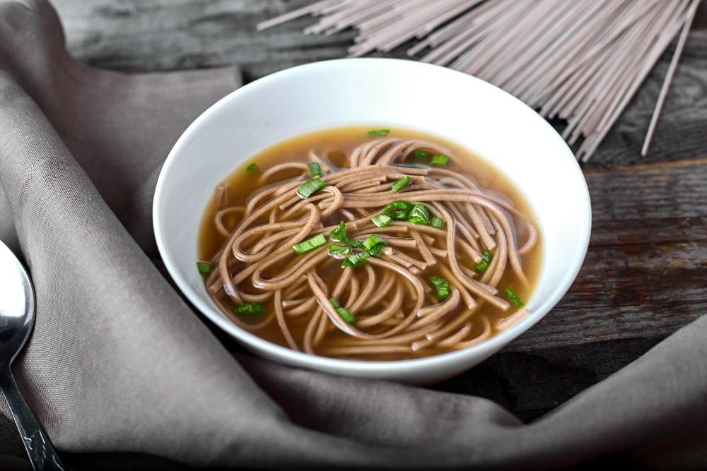 Разливаем по тарелкам и украшаем луком легкий суп в азиатском стиле с гречневой лапшой и лососем