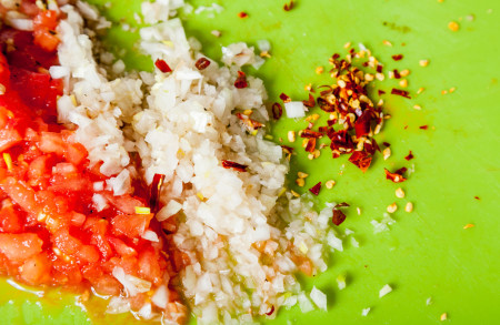 Chopping the other half of an onion and 1 dry chili pepper too for Mexican Lime Soup