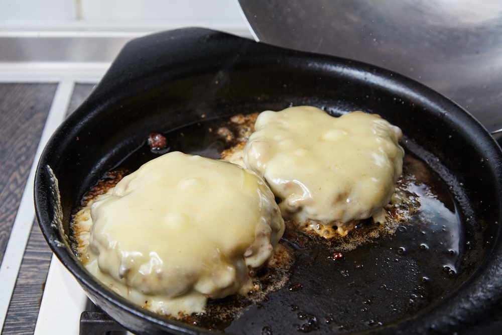 Melt the cheese for Classic cheeseburger with caramelized onion