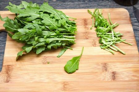 Отрезаем стебли рукколы для салата из рукколы с карамелизированными персиками