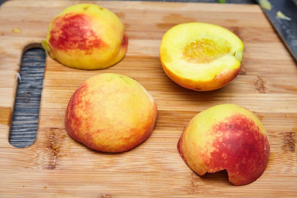 2 персика разрезаем пополам и вынимаем косточку для салата из рукколы с карамелизированными персиками