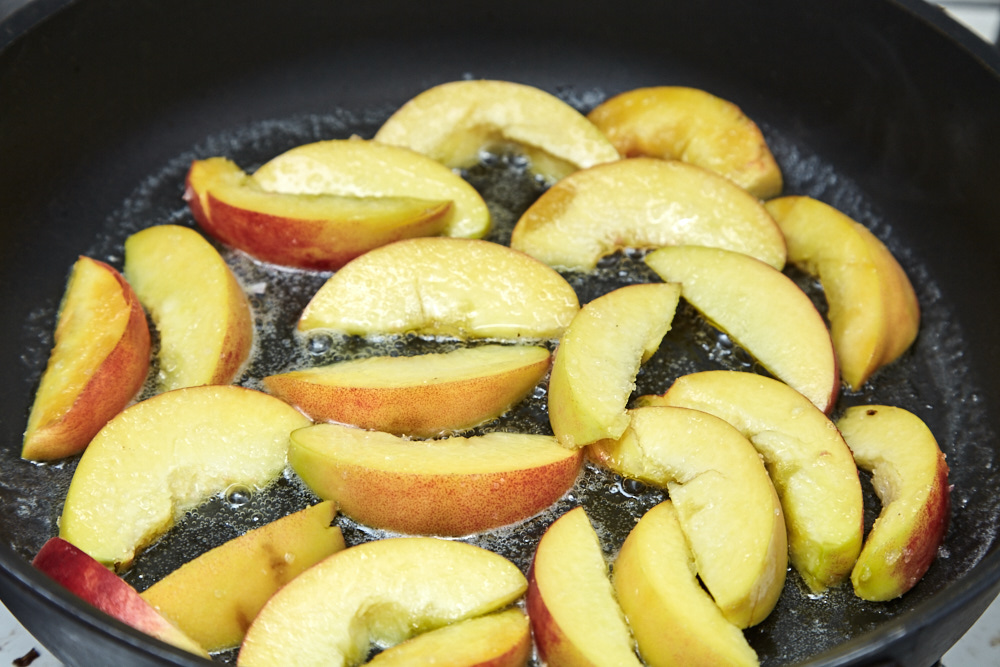 Put the peaches on the frying pan for arugula salad with caramelized peaches
