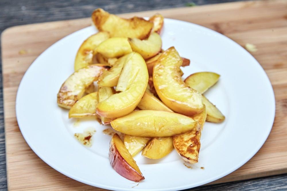 Выкладываем персики на тарелку и даем остыть для салата из рукколы с карамелизированными персиками