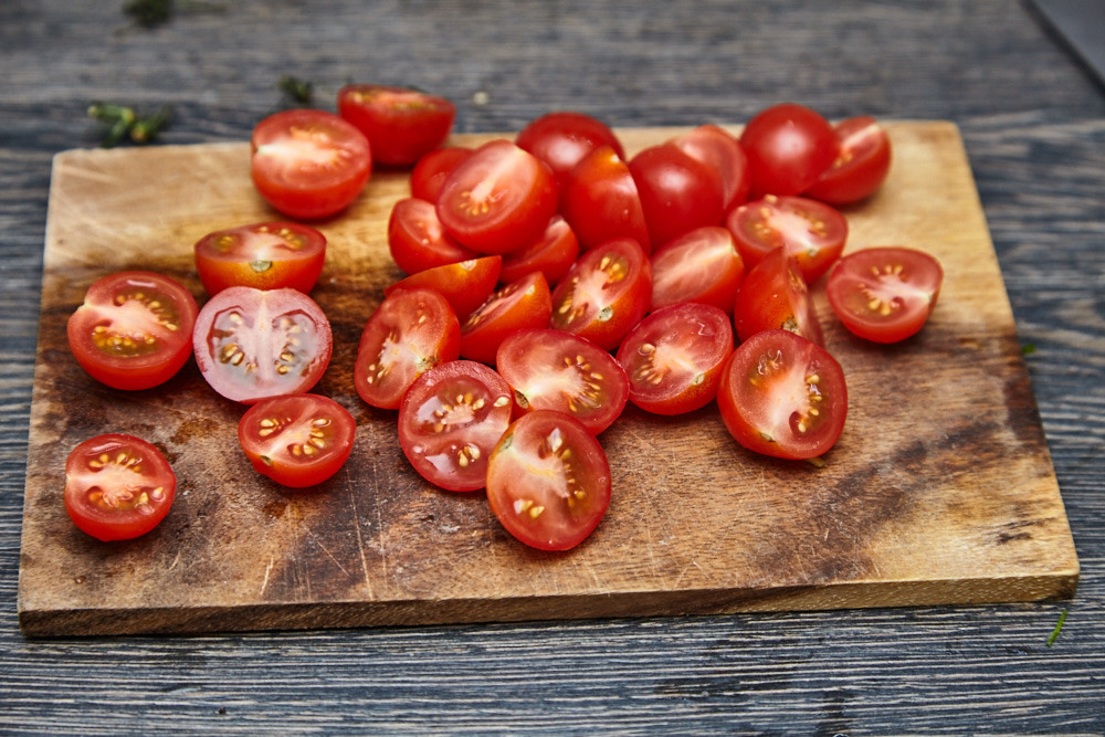 Wash cherry tomatoes and cut them in half for arugula salad with cherry tomatoes and parmesan