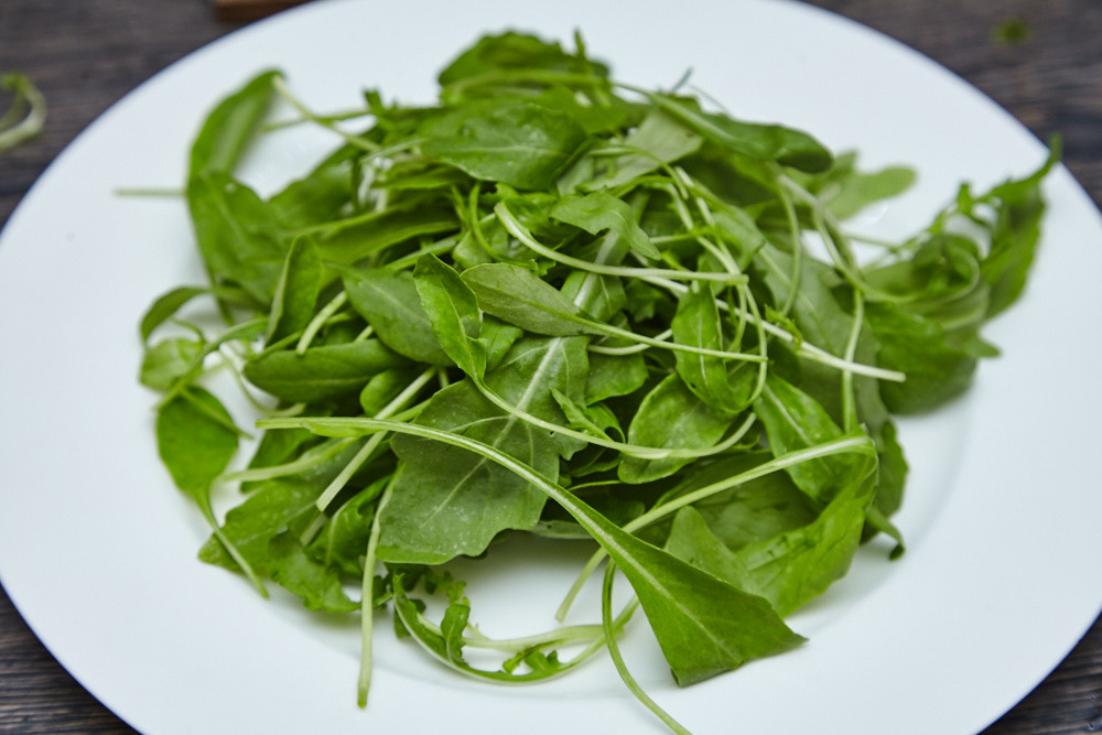 Place the arugula leaves on the plate for arugula salad with cherry tomatoes and parmesan
