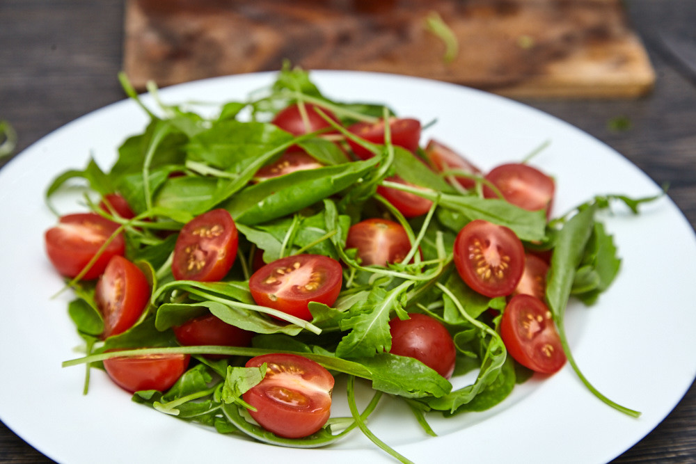 Scatter sliced tomatoes on top for arugula salad with cherry tomatoes and parmesan