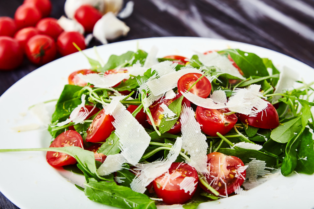 Add a lemon juice and richly sprinkle with olive oil for arugula salad with cherry tomatoes and parmesan