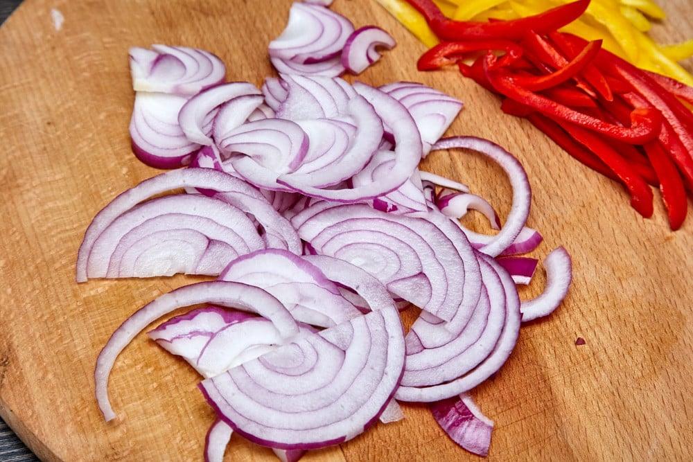 Нарезаем 1 луковицу полукольцами для свинины на подушке из сладкого перца
