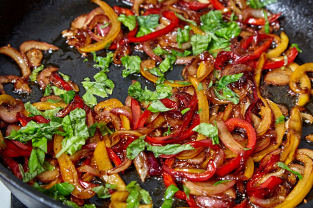 Add chopped basil to the peppers for pork with a sweet pepper