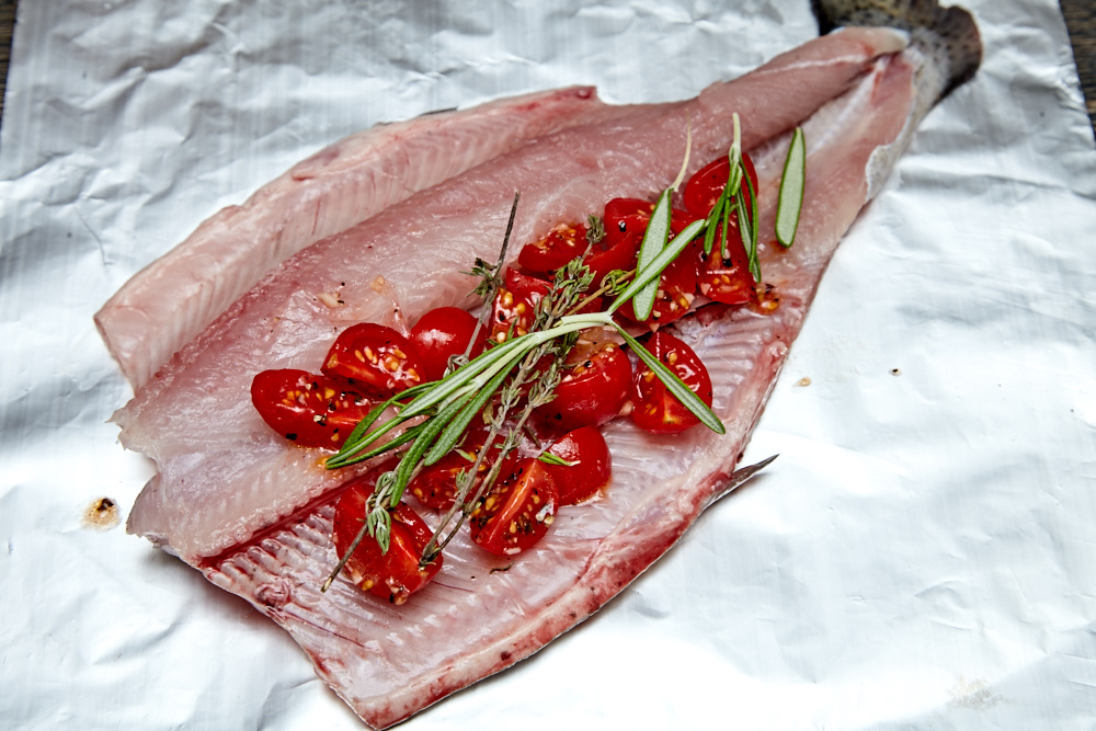 Put a half of tomatoes on top, a few thyme twigs and a rosemary twig for rainbow trout with Herbs and Tomatoes in the Foil