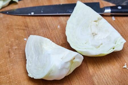 Половину капусты разрезаем пополам для капустного салата коул слоу от Джейми Оливера