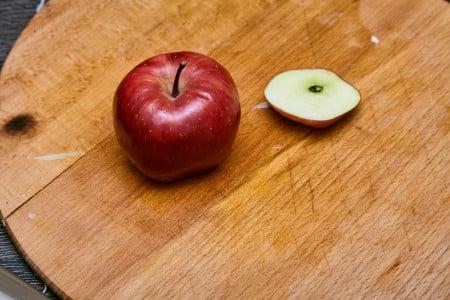 Срезаем у яблока нижнюю часть для придания дополнительной устойчивости для капустного салата коул слоу от Джейми Оливера