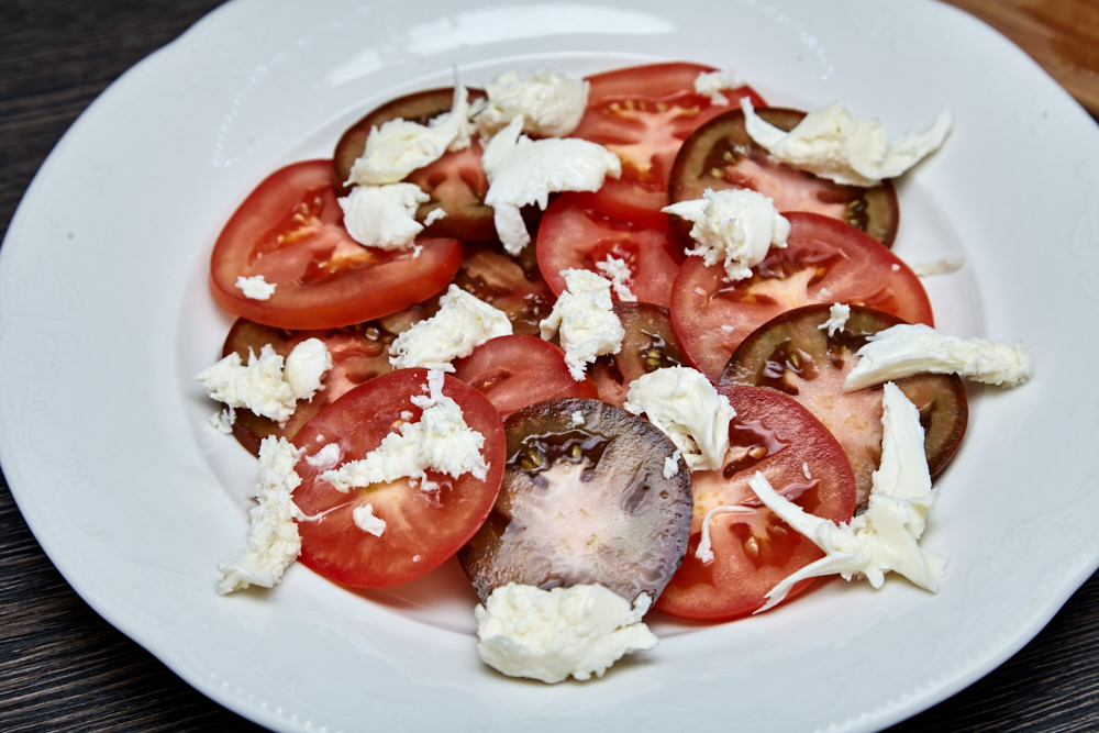Alternate the cheese with tomatoes or just place evenly on top for classy caprese salad