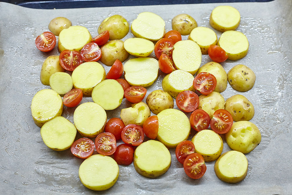 Place the mixed tomatoes and potatoes on the baking sheet for gentle chicken breasts baked with vegetables in balsamic-honey marinade