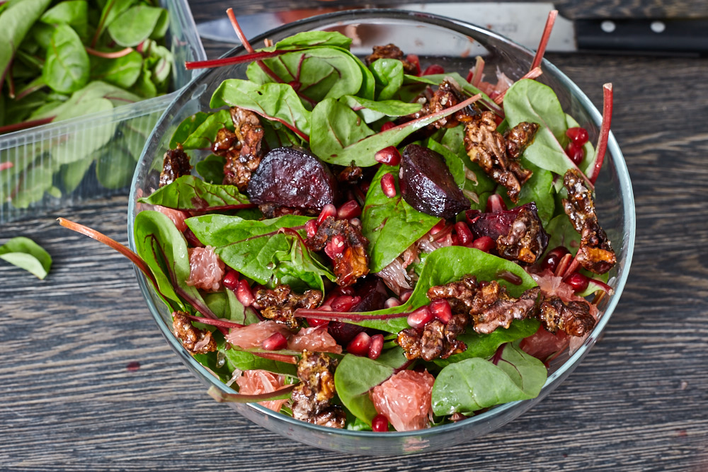 Add caramelized nuts and a half of pomegranate grains on top for beetroot and spinach salad with caramelized nuts and citrus vinaigrette dressing