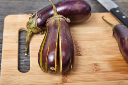 Прорезаем баклажаны вдоль не дорезая до хвостика, на пластинки толщиной около 1 см. для веером запеченных баклажанов с помидорами и сыром фета