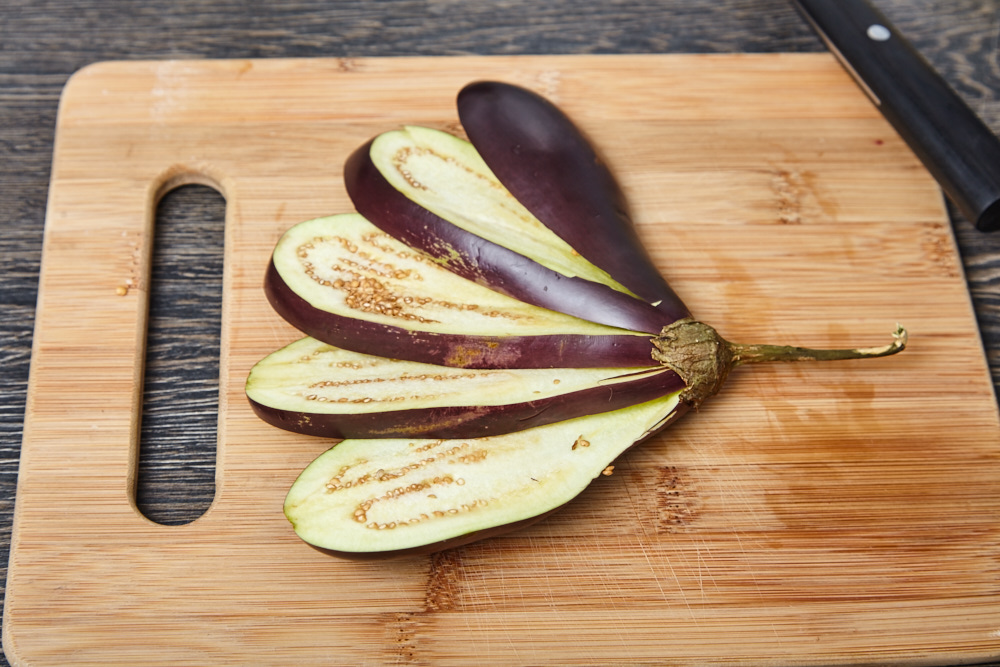 Lay out the eggplants like a fan for fan shaped baked eggplants with tomatoes and feta cheese