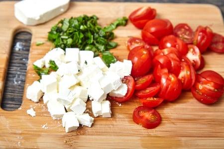 Нарезаем базилик и сыр фета для веером запеченных баклажанов с помидорами и сыром фета