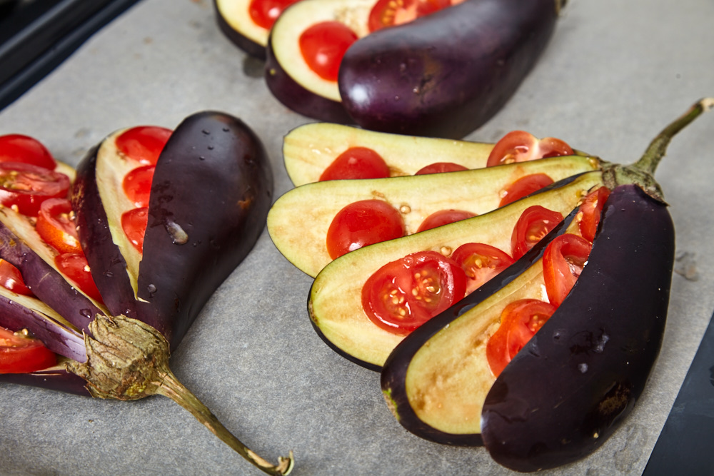 On every slice put 3-4 pieces of cherry tomatoes for fan shaped baked eggplants with tomatoes and feta cheese