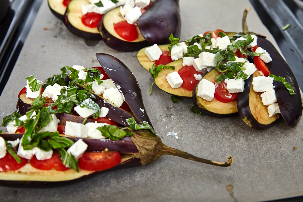 Then add Feta, garlic, and basil leaves on top for fan shaped baked eggplants with tomatoes and feta cheese
