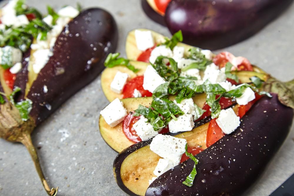 Солим, перчим и щедро поливаем оливковым маслом для веером запеченных баклажанов с помидорами и сыром фета
