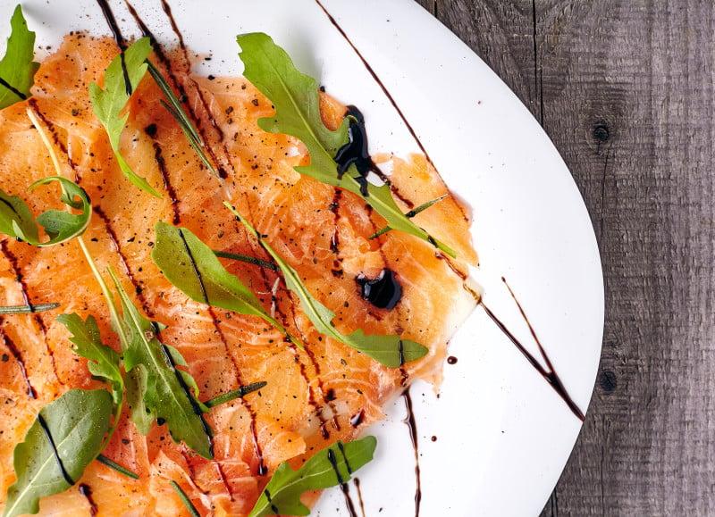 Сбрызгиваем блюдо бальзамиком, солим, перчим, украшаем рукколой для карпачо из лосося с дыней