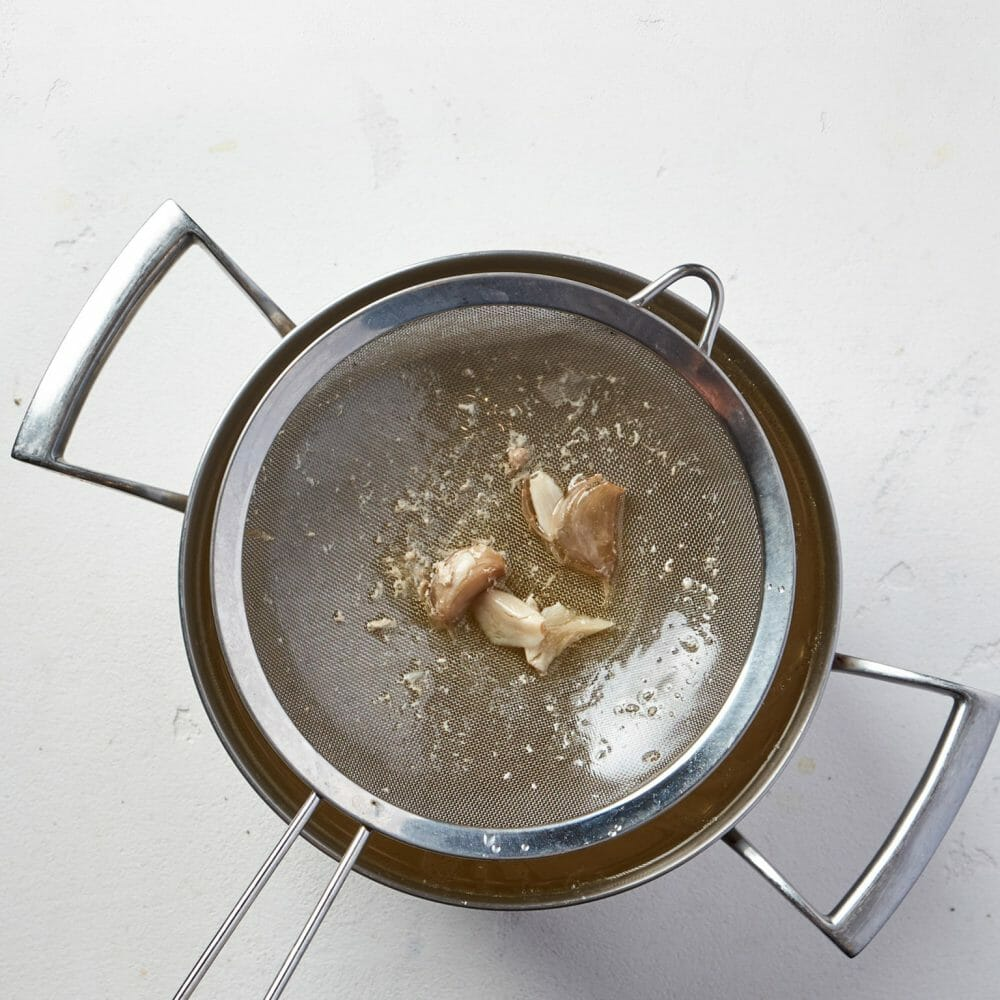 Step3-Strain through a sieve, cool, and pour it into containers. Put in the fridge. - Basic Chicken Stock Recipe copy