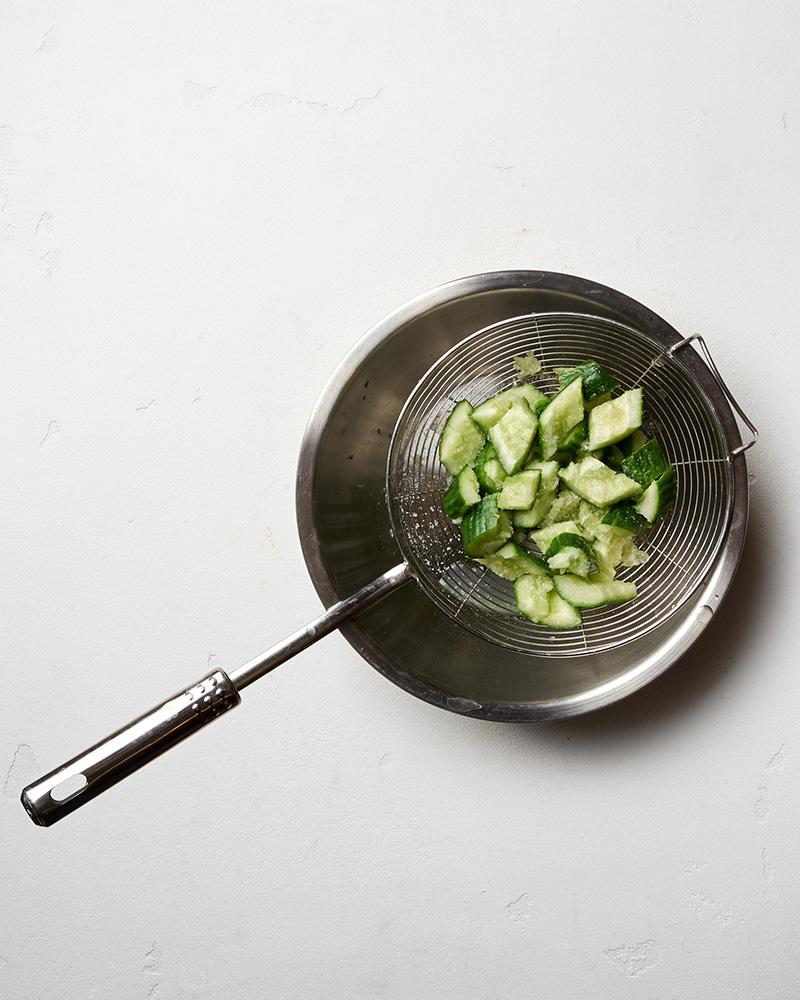 Переложите нарезанный огурец в сито. Сито поставьте на миску, куда будет стекать сок.
