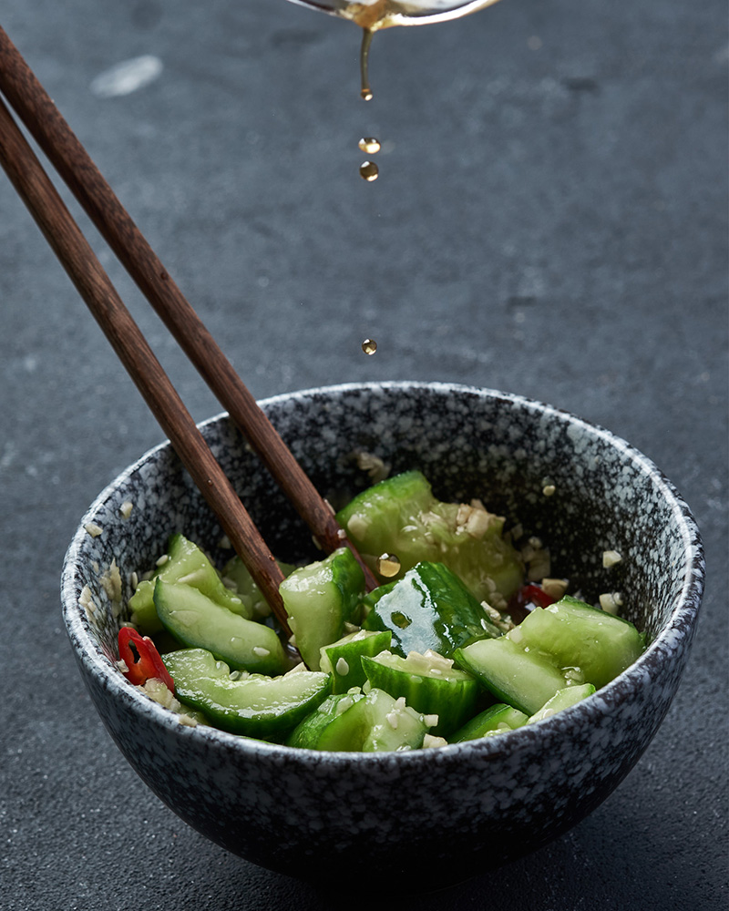 After 15 minutes, transfer the cucumbers to a serving plate, pour half of the dressing over them, and stir.
